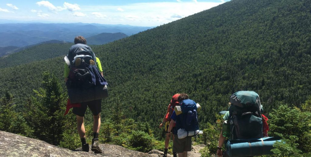 Backpackers descending down a mountain in the Adirondacks.